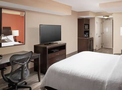 A hotel room with a white bed, TV desk and chair