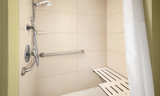 a roll-in shower with a bench