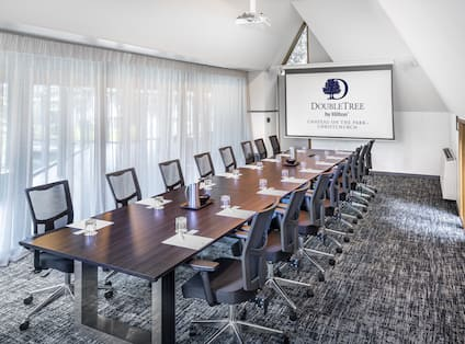 a boardroom table and a presentation screen in a meeting room