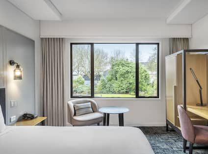 a bed and a chair by a window
