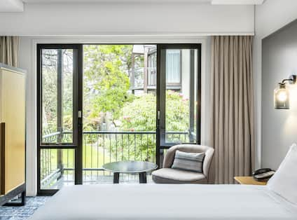a bed and chair in a guest room with a balcony