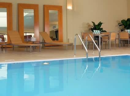 Tables, Chairs, Three Full Length Mirrors, and Relaxation Loungers by Indoor Pool