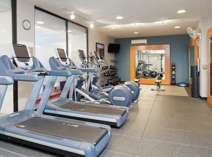 Fitness Center With Cardio Equipment, TV, Free Weights, Large Mirrors, Weight Bench, Weight Balls, and Water Cooler