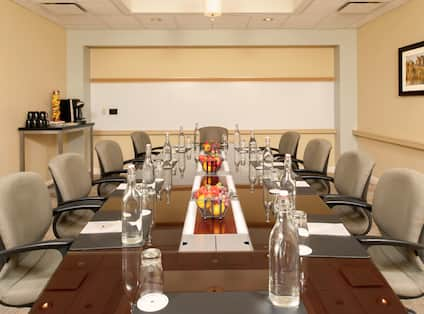 Water Pitchers, Bowls of Fruits, Notepads, and Chairs at Boardroom Table
