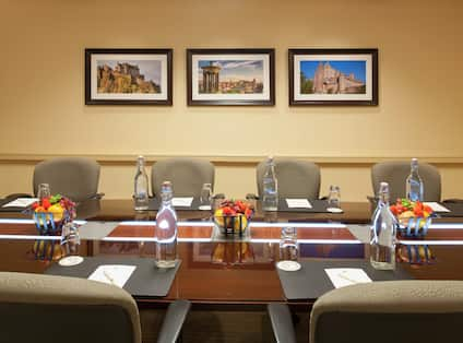 Bowls of Fruit, Water Pitchers, and Notepads on Tables With Chairs and Wall Art in Boardroom