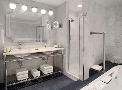 Goldcoast Suite Bathroom with Mirror, Dual Vanity, Walk-In Shower, and Bathtub
