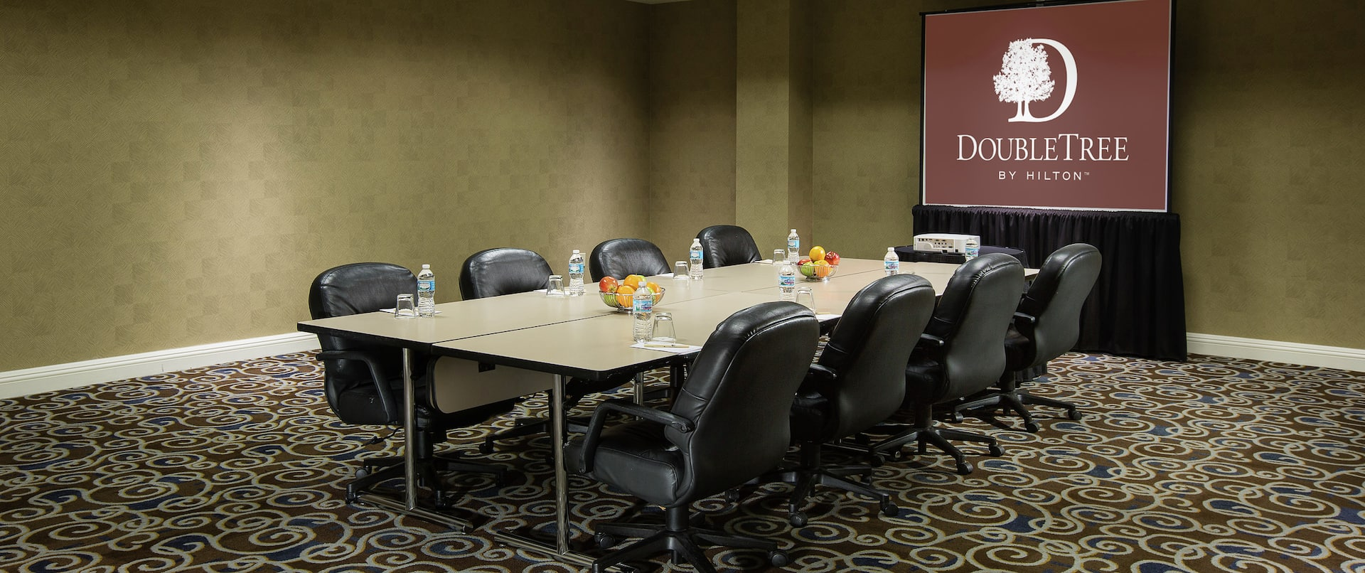 Meeting Room With Presentation Screen and Seating For Eight at Boardroom Table