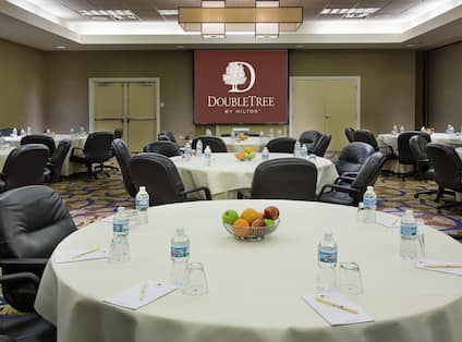 Bottled Water, Notepads, Pens, and Bowls of Fruit on Round Tables With White Linens in Meeting Room With Projector Screen