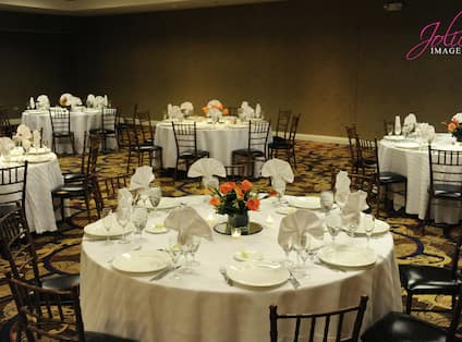 Round Dining Tables With Place Settings and Flowers on White Linens Set Up For a Wedding Reception