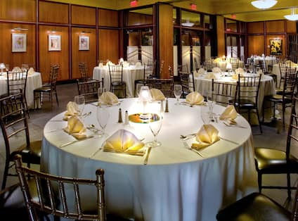 Round Dining Tables With Place Settings and White Linens in Gibsons Steakhouse