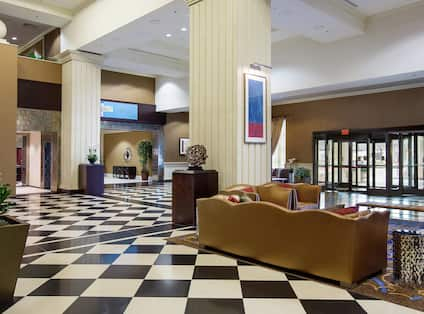 Spacious Lobby With Checkered Floor. Lounge Seating and Glass Entrance Doors