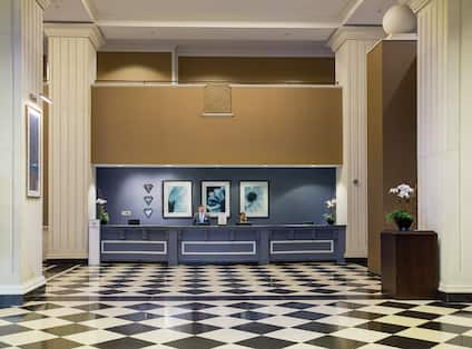 Wall Art and Two Staff Members Behind Front Desk in Lobby With Checkered Floor