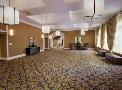 Lounge Area Outside Ballroom Foyer With Soft Seating and Large Windows With Long Drapes