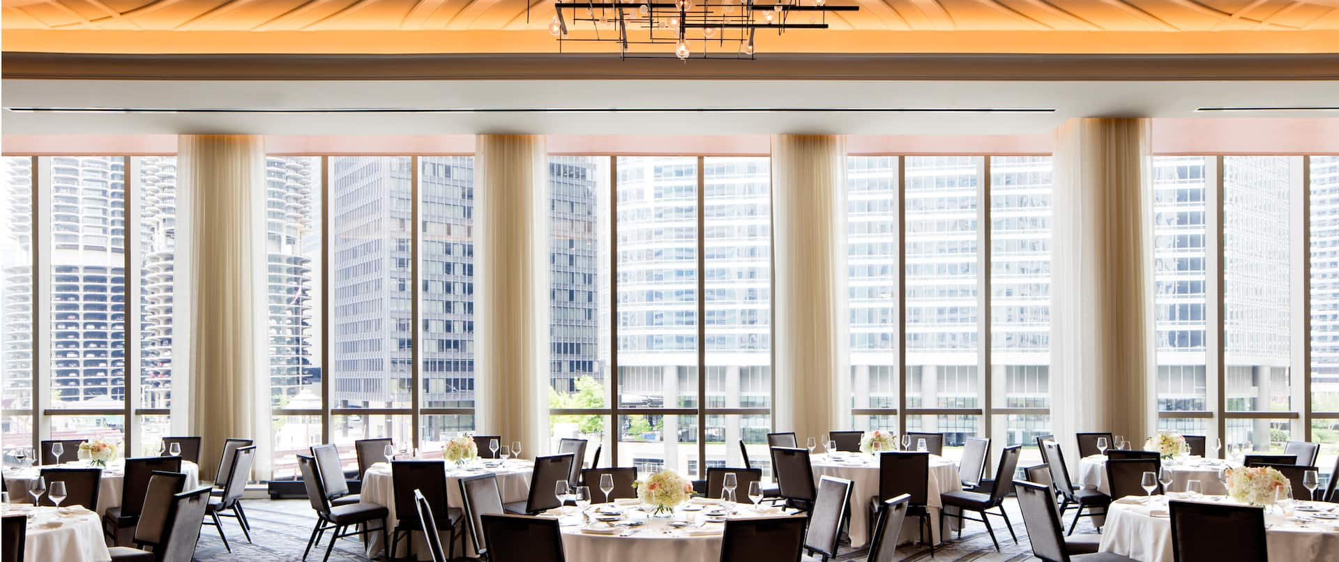 Naturally lit Ballroom Set with Round Tables Showing Designed Ceilings and Columns Near Floor to Ceiling Windows