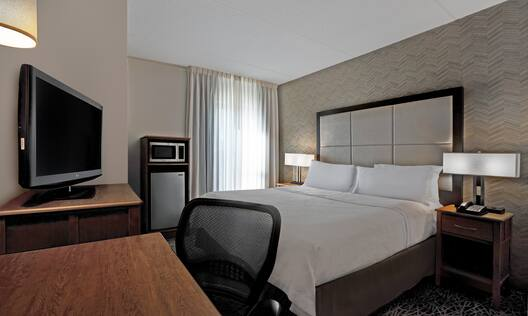 guest room with bed work desk television and window