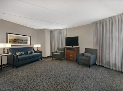 guest room lounge area with television and windows