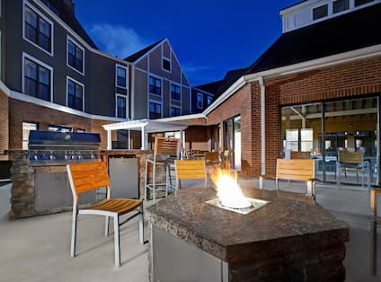 exterior patio with barbeque and fire pit at dusk