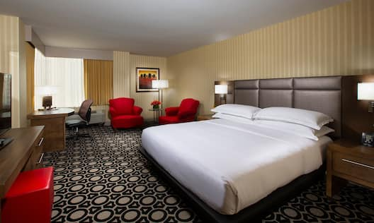 Bed in room with red chairs and workdesk