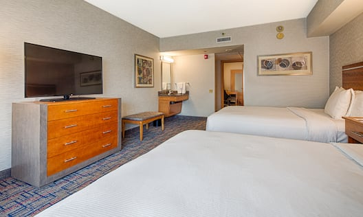 Bedroom with two beds, TV, and wetbar