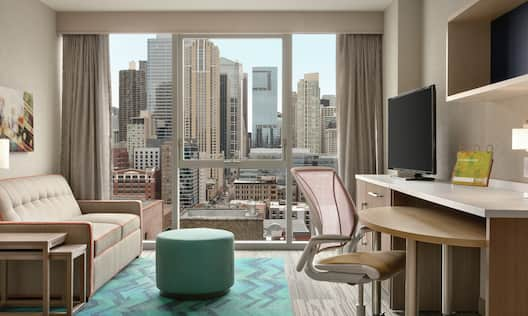 Suite Living Room with Large Windows Offering City View, and Sofa TV and Desk