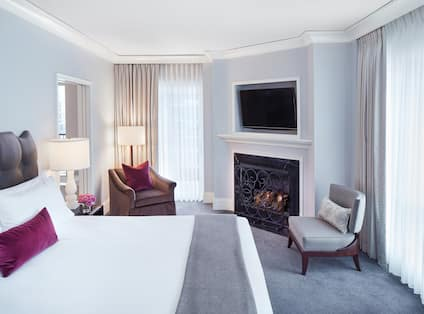 King bed and lounge area with fireplace