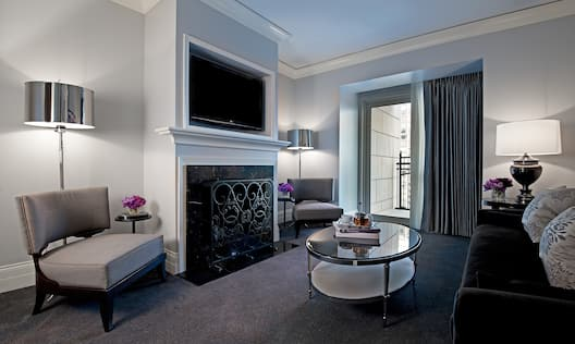 Astoria Suite lounge area with fireplace and flatscreen TV