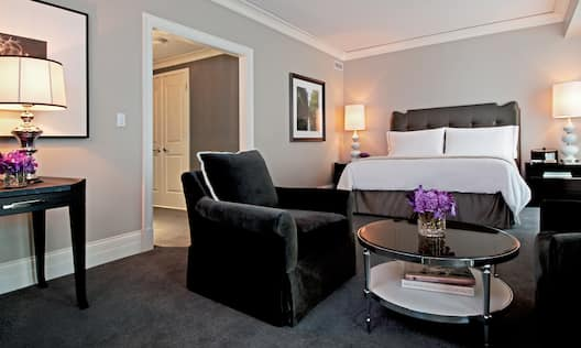Large Bed Armchair and Small Table in Guest Room