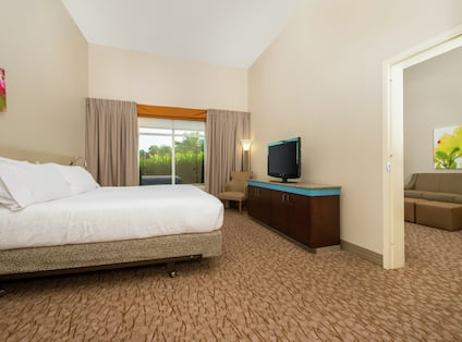 Guest room with bed, TV and separate lounge seating area.