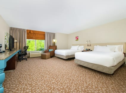 Guest room with two beds, TV and window.