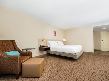 Guest room with bed and lounge chair.