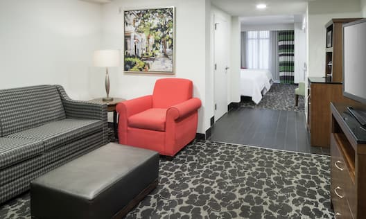 Jr. Suite Living Area with pull out sofa, red sitting chair and TV