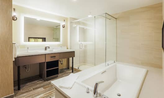 Bathroom with Lit up Mirrored Vanity Double Sink, Oversized Tub and Walk-In Shower