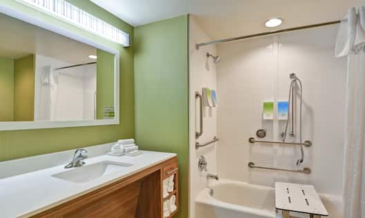 Shower and Bathtub with Transfer Seat, Handrails, and Handheld Showerhead in Accessible Suite Bathroom