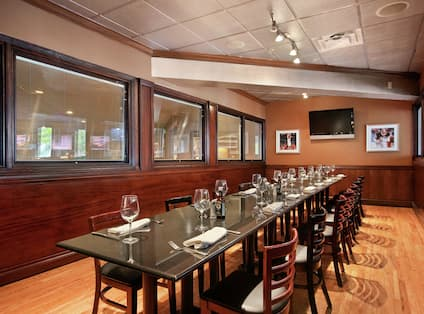 TV, Long Dining Table and Chairs in Shula's Steak Restaurant Private Dining Room