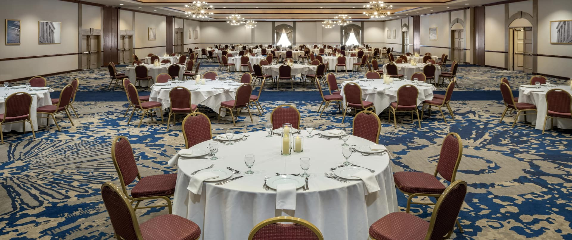 Spacious grand ballroom featuring banquet tables with beautiful linens, table settings, and candles.
