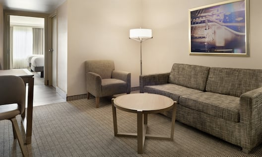 Bright living area in suite featuring sofa, dining table, and view into private bedroom with two double beds.