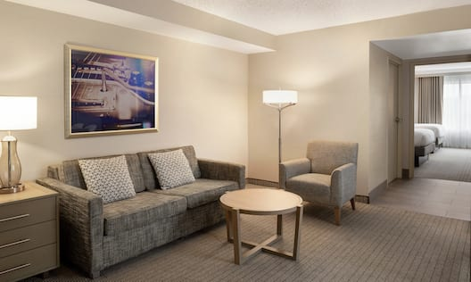 Spacious lounge area in corner suite featuring sofa and view into private bedroom.