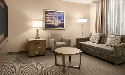 Spacious lounge area in accessible room featuring comfortable sofa and TV.