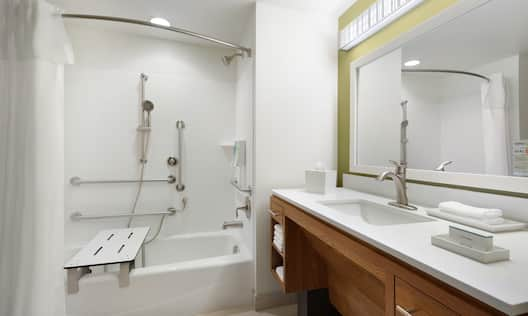 Vanity/Sink with Mirror, Towels, Toiletries, and Tub with Seating and Handrails in Accessible Bathroom