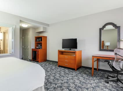 Bed, Work Desk With Ergonomic Chair, Flat Screen TV, And Beverage Station With Microwave And Mini-Fridge Guest Room