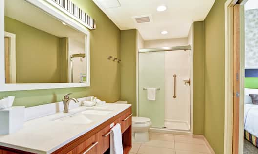 Vanity and Shower with Sliding Frosted Glass Doors in One Bedroom Suite Bathroom