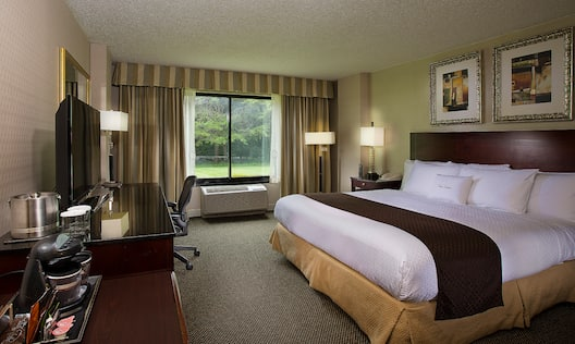 King Bed, Hospitality Center, TV, Work Desk, and Window With Open Drapes in Guest Room