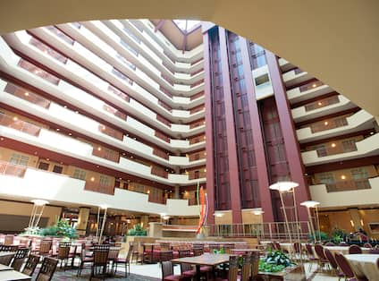 Hotel atrium with large dining area and view of multiple floor banisters