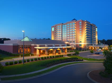 Front hotel exterior with circle drive under covered entrance, lit up at dusk