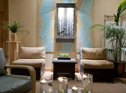Spa Botanica waiting area with soft chairs, plants, and candles