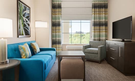 Guest Room Lounge Area with Sofa, Coffee Table, Armchair and HDTV