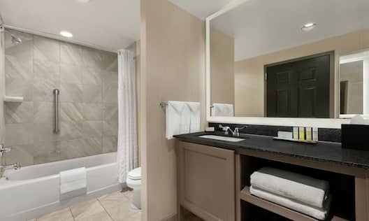 Suite Bathroom with Accessible Tub Stocked with Toiletries