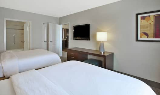 Two Queen Beds, View Into Bathroom, View Into Living Room and TV in Suite Bedroom