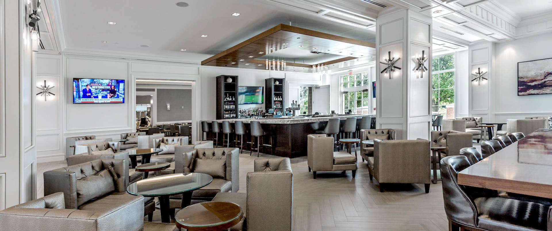 Hotel social space with bar, soft chairs, dining tables and chairs, TV, and floor-to-ceiling windows with outdoor view