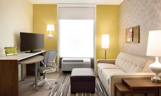 Guest Room Suite Lounge Area with Sofa, Footrest, Work Desk and HDTV
